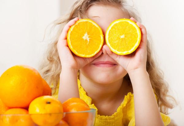 Kind mit Orangen auf den Augen