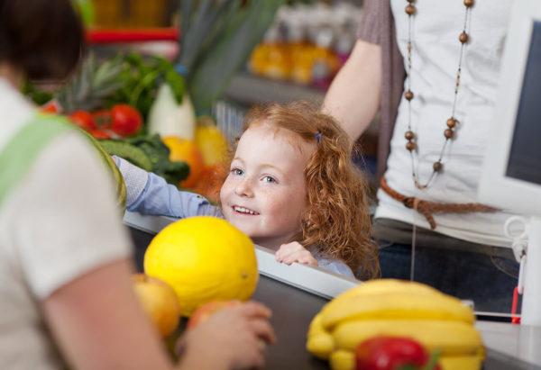 Kind am Kassenband vom Supermarkt